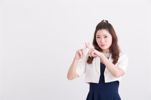 両手の人差し指で×印を作る女性